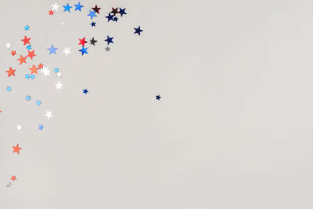 Festive background with confetti in the shape of stars in the color of the American flag. US independence day.