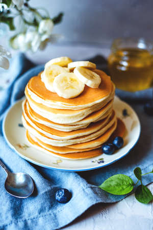 A stack of pancakes with fresh banana, blueberry and honey. Delicious homemade breakfast.