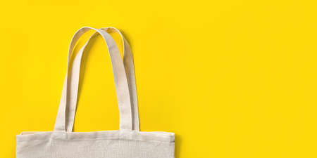 Fabric eco bag on yellow background. Flat lay, top view. Eco friendly concept.