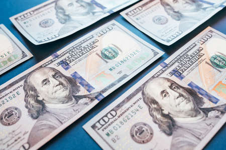 American cash dollars. Hundred-dollar bills in hand on blue background.