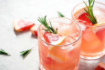 Refreshing grapefruit cocktail with ice and rosemary on a grey background. Stock Photo