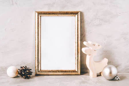 Golden photo frame and christmas decorations on gray background. Christmas, winter, new year concept. Copy space for text.