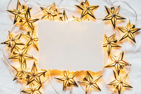 Greeting card for Christmas or New year of golden garlands in the shape of stars with a paper card-note. Flat lay. Minimal concept.