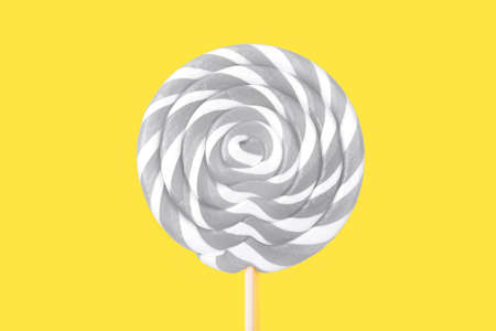 Gray lollipop in the shape of a circle on a yellow background. Flat lay, top view.