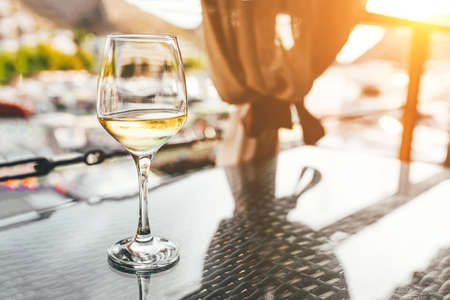 A glass of white wine on the table of a summer cafe. Foto de archivo
