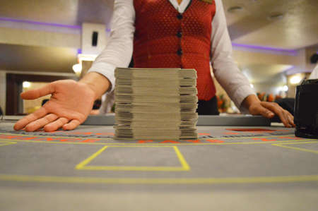 real casino croupier at blackjack card game table photo