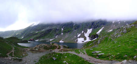 balea: Balea Lake in the clouds and snow near transfagarasan road