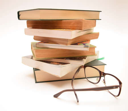 novel and poetry books and eyeglasses isolated on white background