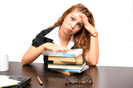 unmotivated: tired girl studying with books on the table isolated on white background