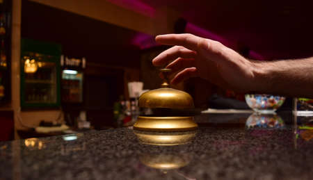 front desk: man hand ring the bell at the hotel front desk Stock Photo