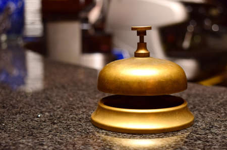 front desk: call bell made of bronze at a hotel front desk