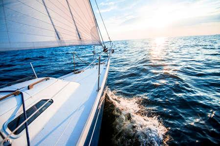 Segeln bei Sonnenuntergang. Ein Blick vom Deck der Yacht auf den Bug und die Segel. Vereinigtes Königreich