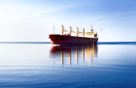 General cargo ship sailing in still water with its reflection near the port of Riga. Baltic seaGeneral cargo ship sailing in still water with its reflection near the port of Rotterdam