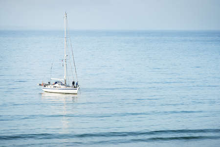 White yacht setting off the anchor in a bay of Celtic sea at the coast of Brittany, France. Panoramic seascape. Sailing, sport, recreation, cruise, leisure activity, nautical vessel, transportation