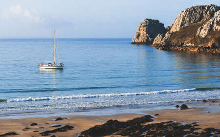 White yacht anchored in a bay of Celtic sea at the coast of Brittany, France. Rocky shores (cliffs) close-up. Panoramic picturesque scenery. Sailing, sport, recreation, cruise, leisure activity