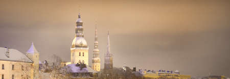 Spiers of Riga Cathedral, St. Peter's Church and St. Savior's Church at night. Panoramic winter cityscape. Christmas vacations in Latvia. Travel, national landmarks, sightseeing, culture, religion