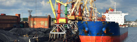 Large blue bulker ship loading coal in the Ventspils free port, Latvia, Baltic sea, Europe. Freight transportation, nautical vessel, fuel generation, global communications, logistics. Panoramic view