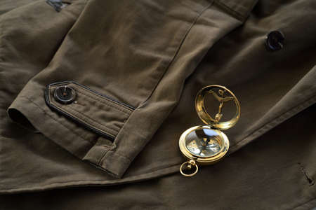 Antiquarian golden compass (sundial) and the old brown overcoat close-up. Vintage still life. Sailing, travel accessories, concept art, collecting, clothes, equipment, graphic resources