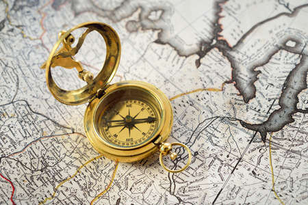 Retro styled golden compass (sundial) and old white nautical chart close-up. Vintage still life. Sailing accessories. Travel and navigation theme