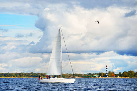 White sloop rigged yacht sailing in Riga bay, close-up. Lighthouse and forest in the background. Dramatic sky. Sport and recreation theme. Baltic sea, Latvia