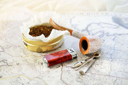 Elegant smoking pipe, tobacco, lighter and accessories, old white nautical chart close-up. Vintage still life. Travel gentleman set. Unhealthy lifestyle, bad habit theme