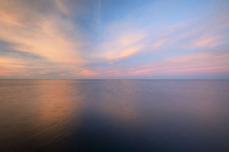 Baltic sea under the colorful sunset sky. Stunning seascape. Golden sunset light through the pink clouds. Long exposure. Tranquility scene. Riga bay, Latvia