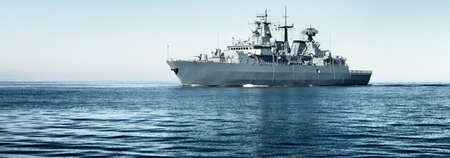 Large gray modern warship sailing in still water. Clear blue sky. Baltic sea, Germany. Global communications, international security theme. Panoramic image