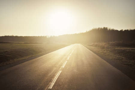 An open highway on a hot summer day at sunset. Forest in the background. Driving a car through the country fields. Leisure activity, recreation theme. Latvia 스톡 콘텐츠