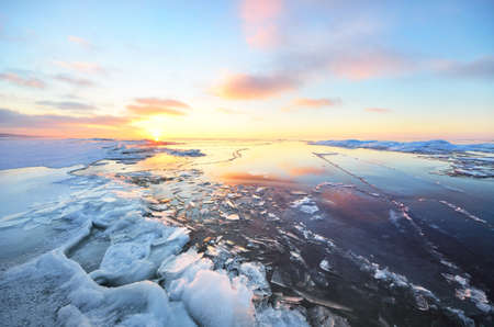 Panoramic view of the snow-covered shore of the frozen Saima lake at sunset. Ice fragments close-up, forest in the background. Colorful cloudscape. Symmetry reflections on the water. Finland