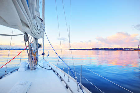 White yacht sailing in a still water at sunset. Frost and first snow on the deck, close-up view to the bow, mast, ropes and sails. Clear blue sky with colorful winter clouds. Norway Foto de archivo
