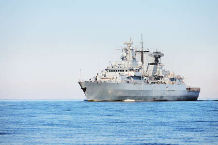 Large gray modern warship sailing in still water. Clear blue sky. Baltic sea, Germany Stockfoto