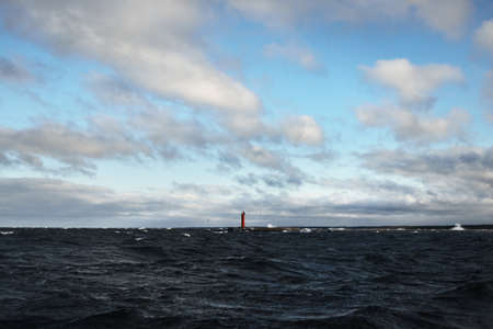 A lighthouse under the dark clouds after the thunderstorm. A view from the sailing boat. Dramatic stormy sky. Epic cloudscape. North sea, Norway. Cyclone in winter. Ecology, global warming concepts