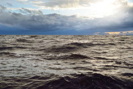A view to the North sea from a sailing boat at sunset. Dramatic stormy sky, sun rays through the dark clouds. Epic seascape. Deep cyclone in winter. Norway