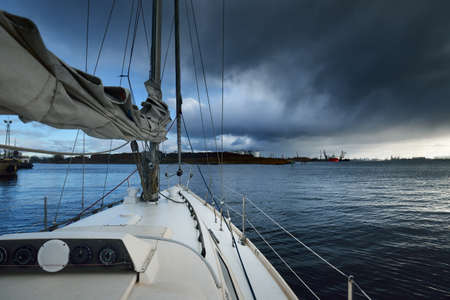 White yacht leaving the river port at sunset, Norway. A view from the deck to the bow and sails. Dramatic sky after the storm. Winter sailing. Leisure activity, recreation theme