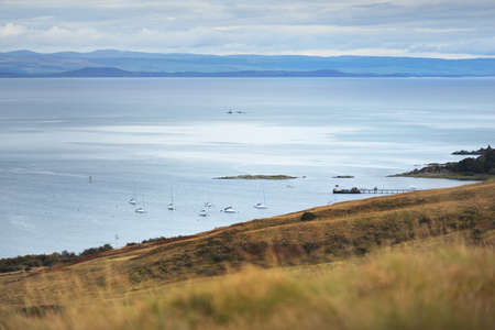 Sloop rigged yachts and fishing boats anchored on mooring near the shore of Jura island on a cloudy day. Panoramic aerial view. Craighouse, Inner Hebrides, Scotland, UK