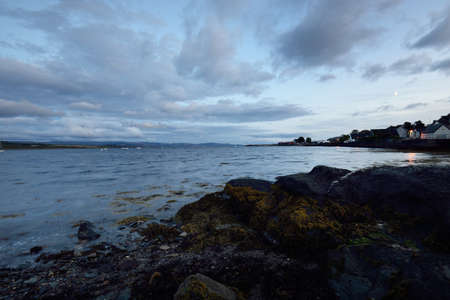 Panoramic view of the lake shores, valleys, hills and forests under ornamental stormy clouds. Twilight sky. Ardrishaig, Crinan canal, Scotland, UK. Nature, ecology, environmental conservation