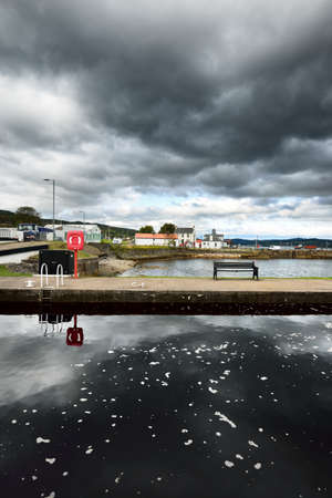 A small harbor and empty promenade to the old lighthouse, close-up. Rocky shores in the background. Dramatic cloudscape. Ardrishaig, Crinan canal, Scotland, UK. Travel destinations, sightseeing theme