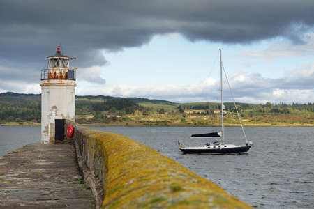 Black sloop rigged yacht sailing near the lighthouse in Crinan canal on a cloudy day, close-up. Rocky shores in the background. Dramatic blue sky. Ardrishaig, Scotland, UK. Sport and recreation theme Zdjęcie Seryjne