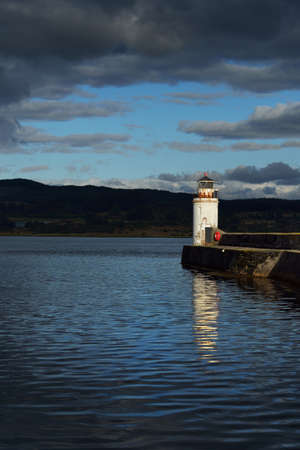 Panoramic view of the rocky shores and forests of a small village Ardrishaig. Promenade and the lighthouse close-up. Loch Fyne, Crinan canal, Argyll and Bute, Scotland, UK