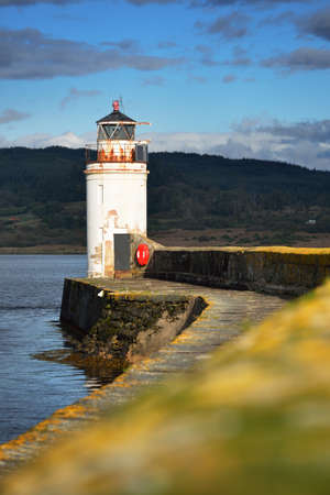 An empty promenade to the old lighthouse, close-up. Rocky shores in the background. Dramatic cloudscape. Ardrishaig, Crinan canal, Scotland, UK Zdjęcie Seryjne