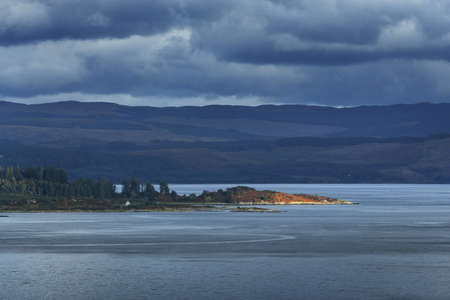 Rocky shores, cliffs, mountain peaks, woodland and hills of Crinan, panoramic aerial view. Ardrishaig, Argyll and Bute, Scotland, UK. Autumn landscape. Dramatic sky. Travel destinations, tourism