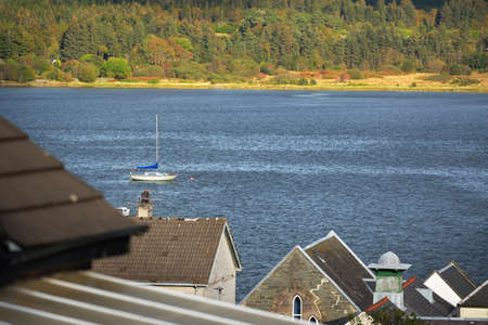 Panoramic view of the rocky shores and forests of a small village Ardrishaig. Yachts and country houses close-up. Loch Fyne, Crinan canal, Argyll and Bute, Scotland, UK