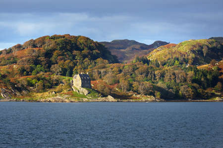 An old traditional brick house on the rocky shore of Crinan canal. Hills and forest in the background. Dramatic cloudscape. Travel destinations, national landmark theme. Scotland, UK