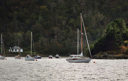 Sloop rigged yachts anchored on mooring near the rocky shore of Crinan canal. Forest hills in the background. Argyll and Bute, Scotland, UK