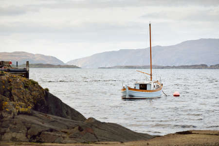 Sloop rigged wooden yacht anchored on mooring near the rocky shore of Crinan canal on a cloudy day. Argyll and Bute, Scotland, UK