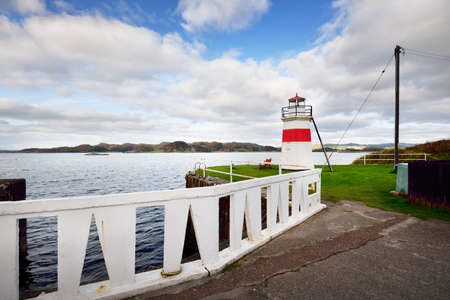 A promenade to the decorative lighthouse on the rocky shore of Crinan canal. Hills and forest in the background. Dramatic cloudscape. Travel destinations theme. Scotland, UK