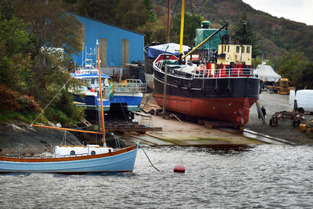 Sloop rigged wooden yacht anchored on mooring near the rocky shore of Crinan canal, fishing boats close-up. Argyll and Bute, Scotland, UK