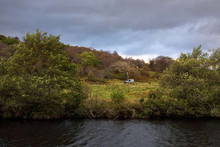 A view of a small town Cairnbaan on a cloudy day. Autumn forest close-up. Crinan Canal, Argyll and Bute, Scotland, UK Zdjęcie Seryjne