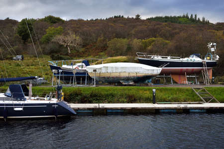 A view of a small town Cairnbaan on a cloudy day. Yachts and fishing boats close-up. Crinan Canal, Argyll and Bute, Scotland, UK