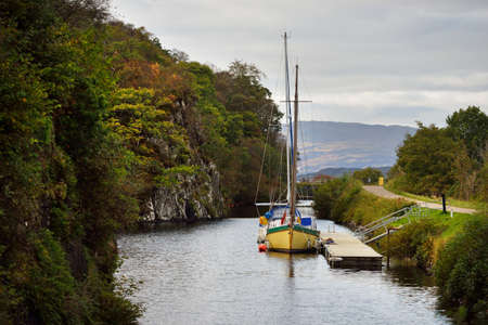 A view of the Crinan canal on a cloudy day. Country houses and yachts close-up. Argyll and Bute, Scotland, UK